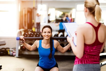 Close up of an attractive fit woman in blue singlet exercising in a gym with her personal trainer writing into exercise plan on clipboard