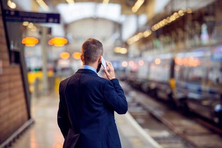 Hipster zakenman met smartphone, het maken van een telefoontje, te wachten op het station platform, terug bekijken, achter, gezichtspunt Stockfoto