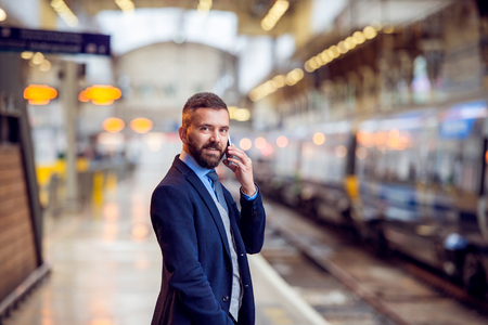 businessman waiting call: Hipster businessman with smartphone, making a phone call, waiting at the train station platform