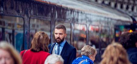 tube station: Hipster businessman walking at the station, crowded underground platform, train Stock Photo