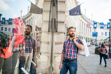 buss: Young hipster man in checked shirt shopping, holding a bag, in the streets of London