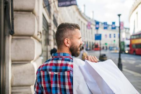 personas en la calle: hombre inconformista joven en compras camisa a cuadros, con sus bolsas de, en las calles de Londres, vista posterior, el punto de vista trasera Foto de archivo