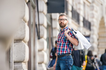buss: Young hipster man with eyeglasses in checked shirt shopping, holding a bag, in the streets of London