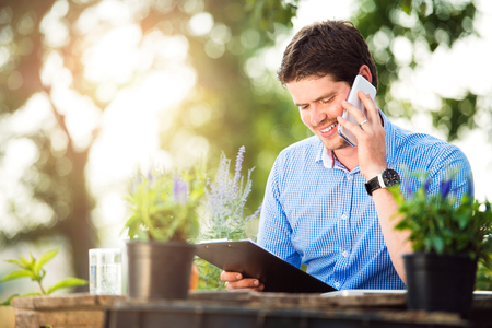 call of nature: Gardener sitting at the table, holding clipboard, making phone call, green sunny nature