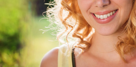 nature beauty: Close up face of unrecognizable blond woman with curly hair in yellow singlet in green nature. Sunny summer.
