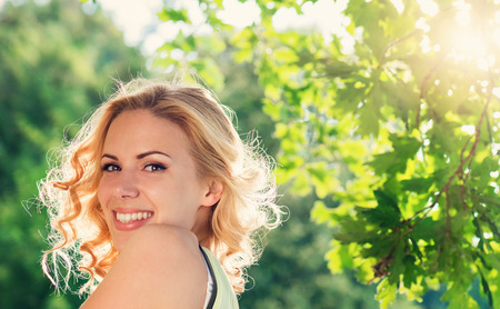 Close up of blond woman with curly hair in yellow singlet in green nature. Sunny summer.