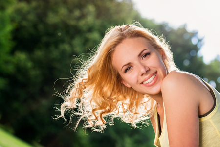 Cerca de la mujer rubia con el pelo rizado que mover de un tirón en el aire en camiseta amarilla en la naturaleza verde. Soleado de verano. Foto de archivo