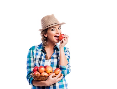 wicker work: Beautiful young woman in blue checked shirt  and hat holding a basket full of apples, eating, biting. Studio shot on white background. Autumn harvest