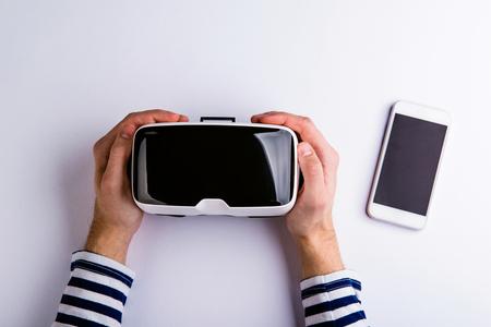 Mains de l'homme tenant des lunettes de réalité virtuelle et téléphone intelligent. à plat. Tourné en studio sur fond blanc.