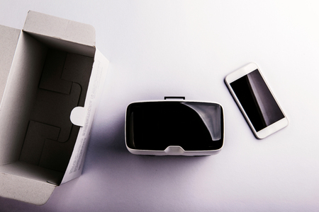VIRTUAL REALITY: Virtual reality goggles, paper box and smartphone laid on a table. Flat lay. Studio shot on white background.