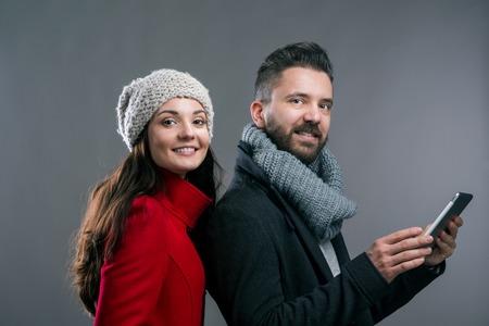 uomo rosso: Donna in cappotto invernale rosso e un uomo pantaloni a vita bassa con sciarpa a maglia con tavoletta. Studio girato su sfondo grigio.