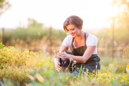 Jonge tuinman in haar tuin met diverse planten, groene zonnige natuur bij zonsondergang