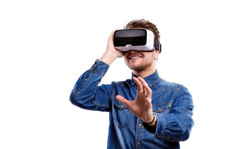 仮想現実を身に着けているデニム シャツの流行に敏感な人はゴーグルします。白い背景で撮影スタジオ