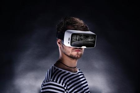 仮想現実を身に着けている黒と白のストライプのトレーナーで流行に敏感な人はゴーグルします。黒の背景で撮影スタジオ