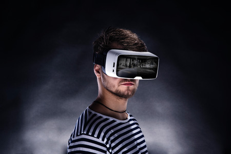 Hipster man in striped black and white sweatshirt wearing virtual reality goggles. Studio shot on black background Standard-Bild