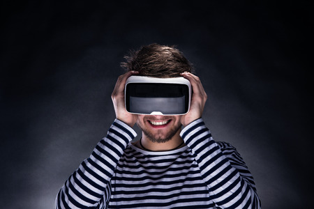 Hipster man in striped black and white sweatshirt wearing virtual reality goggles. Studio shot on black background Banco de Imagens