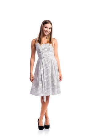 piernas mujer: De pie adolescente en el vestido blanco y negro de puntos, talones, piernas cruzadas, foto de estudio, joven, aislado en fondo blanco