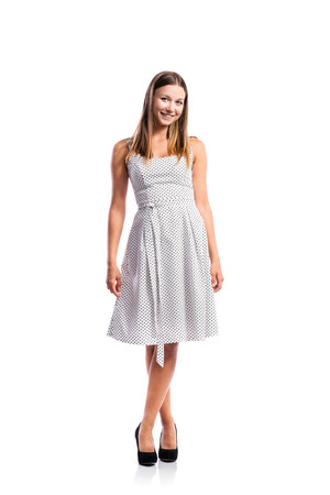 girl legs: Standing teenage girl in black-and-white dotted dress, heels, legs crossed, studio shot, young woman, isolated on white background