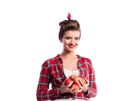 armful: Beautiful young woman in red checked shirt with pin-up make-up and hairstyle holding armful of apples. Studio shot on white background. Autumn harvest