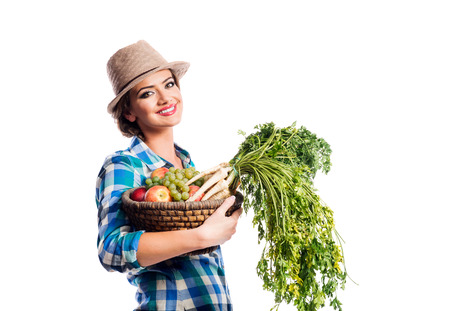 harvest background: Beautiful young woman in blue checked shirt  and hat holding a basket full of vegetables and fruit. Studio shot on white background. Autumn harvest