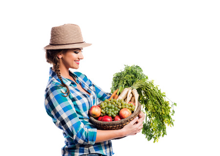 harvest basket: Beautiful young woman in blue checked shirt  and hat holding a basket full of vegetables and fruit. Studio shot on white background. Autumn harvest