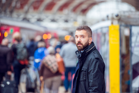 waiting passengers: Young handsome hipster man in black jacket waiting at the crowded train station