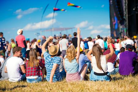 Grupo de adolescentes en el festival de música de verano, sentado en el césped en frente de la etapa