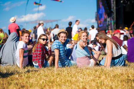 ビュー、後方、視点、バック ステージ前の芝生の上に座って夏の音楽祭では、10 代の若者のグループ