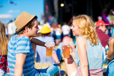 men talking: Young couple at summer music festival, drinking beer, sitting on the grass in front of stage, back view, rear, viewpoint Stock Photo
