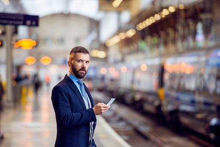 uomo d'affari Hipster con lo smartphone, in attesa alla piattaforma di stazione ferroviaria