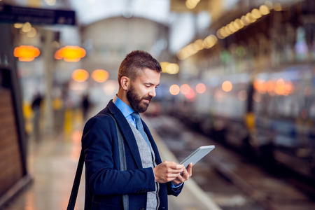 Hipster biznesmen z tabletu, czekając na peronie stacji kolejowej