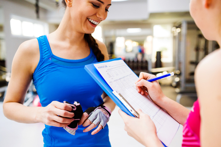 close out: Close up, attractive fit woman in a gym consulting  work out with personal trainer, exercise plan on clipboard