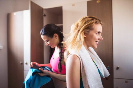 changing room: Two attractive fit woman changing in locker room in gym, workout clothes