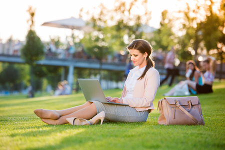 Beautiful young businesswoman sitting in a park on the grass during a lunch break, working on laptop, sunny summer day. Stock Photo