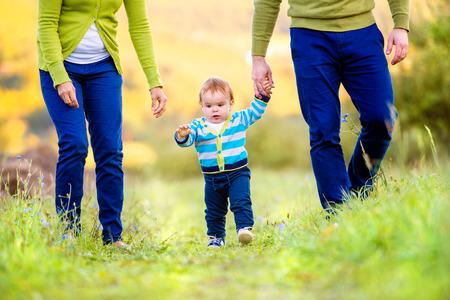 Onherkenbaar moeder en vader holding hands van hun zoontje het maken van de eerste stappen buiten in het groen zonnige karakter