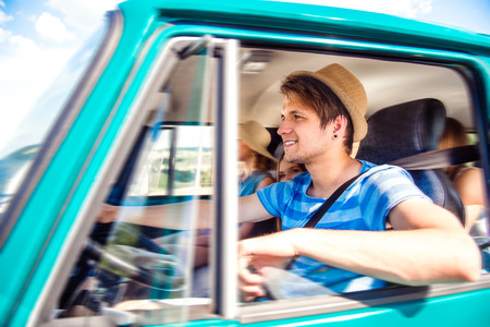 roadtrip: Hipster boy driving an old campervan with teenage friends, roadtrip, sunny summer day