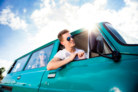 roadtrip: Teenagers inside an old campervan on a roadtrip, boy leaning out of window, sunny summer day Stock Photo