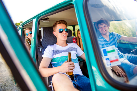 roadtrip: Teenage boys and girls inside an old campervan on a roadtrip, drinking beer, sunny summer day