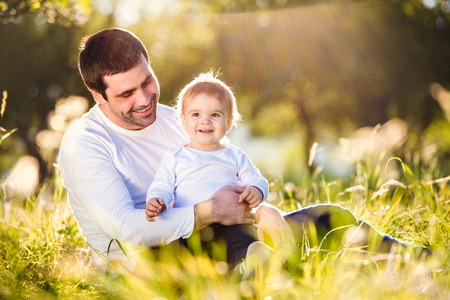 fathering: Father holding his little son, sitting on the grass in sunny nature Stock Photo
