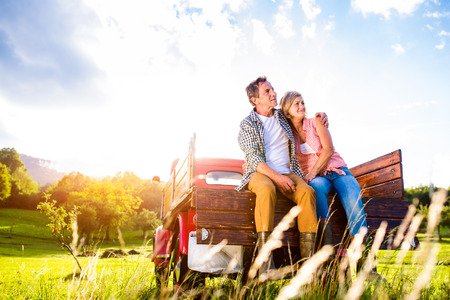 nature green: Senior couple sitting in back of vintage red pickup truck, hugging, green sunny nature Stock Photo