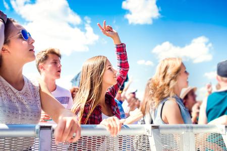 multitud gente: Los adolescentes en el festival de música de verano bajo el escenario en una multitud disfrutando, bailando y cantando