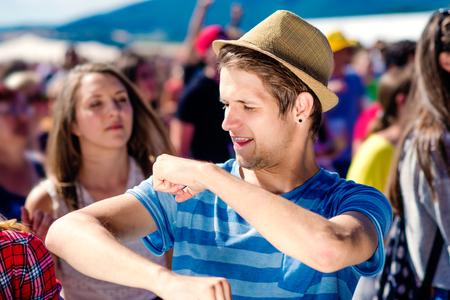 Close-up van tiener jongen in de zomer muziekfestival onder het podium in een menigte zich te genieten, dansen en zingen