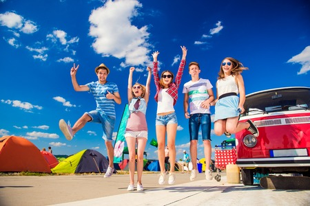 campervan: Group of teenage boys and girls at summer music festival jumping by vintage red campervan