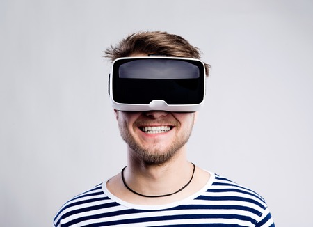 Hipster man in striped black and white sweatshirt wearing virtual reality goggles. Studio shot on gray background Stock fotó