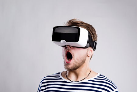 Hipster человек в полосатой черно-белой трикотажной рубашки носить виртуальные очки реальность. Студия выстрел на черном фоне Фото со стока