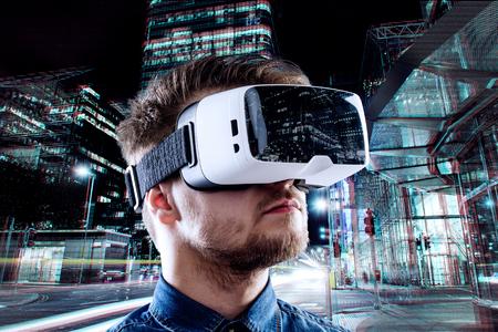 El hombre que llevaba gafas de realidad virtual contra ciudad de la noche iluminada