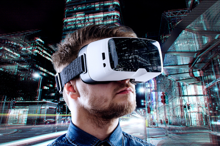 Mężczyzna ma na sobie okulary wirtualne rzeczywistości przeciwko podświetlanym miasto nocą Zdjęcie Seryjne
