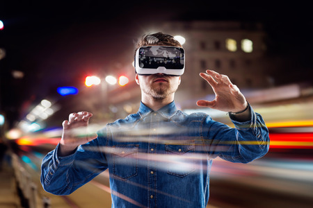 game: Double exposure of man wearing virtual reality goggles and night city Stock Photo