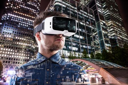 Doble exposición de hombre con gafas de realidad virtual y noche de la ciudad Foto de archivo