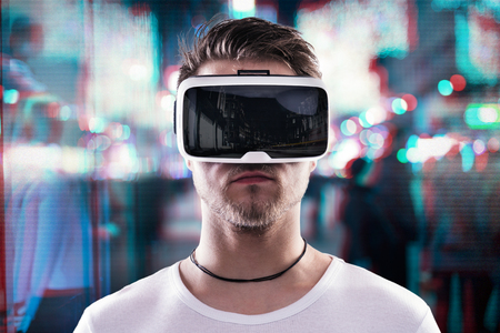 El hombre que llevaba gafas de realidad virtual contra ciudad de la noche iluminada Foto de archivo - 53460577